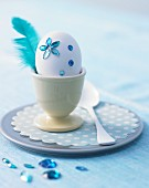 White egg decorated with blue rhinestones & feather in egg cup