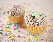 Cupcakes with chocolate cream and colourful chocolate beans