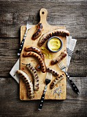 Various grilled sausages with mustard on a chopping board