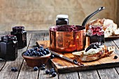 Homemade blueberry jam in a copper pan, glasses and on bread