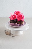 Muffins with chocolate glaze and decorated with roses
