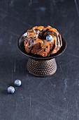 A mini cake with chocolate glaze, caramel sauce and blueberries