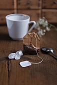 A used tea bag and kluntje rock candy with a tea cup on a wooden table