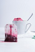 A cup of tea and a used fruit tea bag