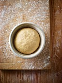 Bread dough in a porcelain dish on a floured wooden board (seen from above)