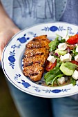 A woman holding a plate of grilled pork collar steak and rocket salad with tomatoes, cucumber and feta cheese