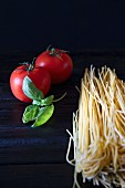 An arrangement of tomatoes, basil and spaghetti