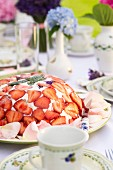 Domed cake decorated with quark and strawberries on table set for afternoon coffee