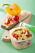 A lunch box with pasta salad and ingredients