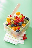 Fruit salad in a lunch box with a fork