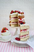 An Eton Mess layer cake with strawberries, raspberries and blueberries, sliced, with a slice on a plate