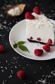 A slice of coconut cheesecake with fresh raspberries