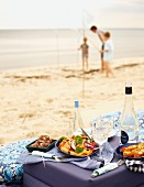 A beach picnic with salad, canapés and drinks