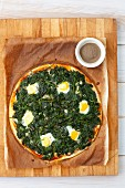 A pizza fiorentina with spinach and quail eggs