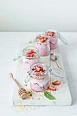 Jars of strawberry yoghurt with honey and mint on a white chopping board