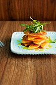 Pancetta chips with honeydew melon, rocket and an orange dressing