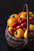 Various different coloured tomatoes in a basket