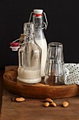 Homemade almond milk in flip-top bottles on a wooden tray