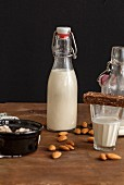 Homemade almond milk in a flip-top bottle and a glass