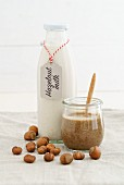 A jar of hazelnut mousse and hazelnut milk in a glass bottle