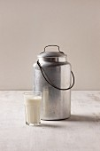 A glass of vegan milk with a metal milk churn