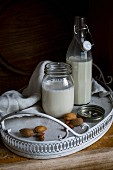 Vegan almond milk in a flip-top bottle and a screw-top jar on a tray
