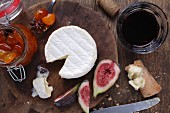 Camembert, chutney and figs on a wooden board (seen from above)