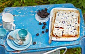 blackberry and meringue slices and coffee crockery on a garden table