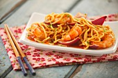 Prawns in a sweet and sour sauce with red onions and noodles