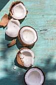 Broken coconuts on a wooden board in sunlight