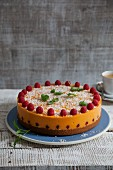 Vegan mango and papaya cake with coconut and fresh raspberries