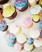 Colourfully decorated cupcakes for a wedding on a multi-tiered cake stand