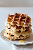 A stack of Belgian waffles with syrup