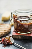 Tomato chutney in a jar and on a spoon