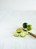 Limes, whole, halved and wedges, with a knife