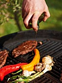 Steak and vegetables on a barbecue being drizzled with olive oil