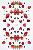 A digital composite of mirrored images of various berries and cherries