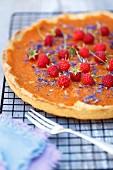 Pumpkin tart with orange marmalade, raspberries and corn flowers