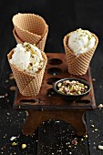 Nut ice cream in ice cream cones in an old egg holder on a dark wooden table