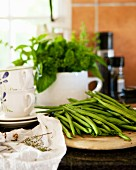 Green beans on a wooden plate in front of porcelain crockery with a herb bouquet