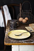 Shortcrust pastry for an apple and frangipane tart being with a fork on a rustic kitchen table