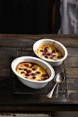 Two portions of freshly baked cherry clafoutis on a cooling rack