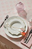 An elegant porcelain place setting with decorative arrows on a pastel pink spotted tablecloth