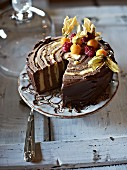 Chocolate cake with physalis and raspberries, sliced