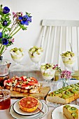 A breakfast buffet with yoghurt cups, cake, toast and grapefruit