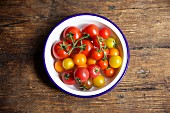 Various tomatoes in bowl on a wooden table
