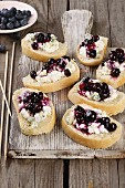 Baguette canapés topped with Gorgonzola cream and blueberries