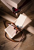 Gift boxes, wrapping paper and wrapped presents with leather ribbon on wooden table