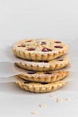 A stack of raspberry tartlets with icing sugar