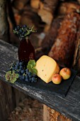 Cheese, apples and grapes on a wooden board in a garden